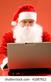Photo of Santa Claus typing e-mail message of congratulation
