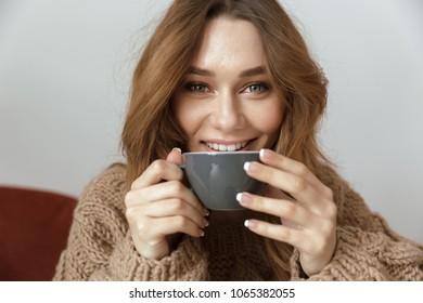 Photo of satisfied and relaxed woman resting at home in living room and drinking cup of tea or coffee with pleasure