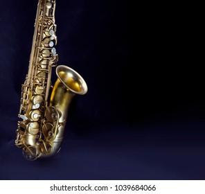 Photo of the saxophone over dark background.