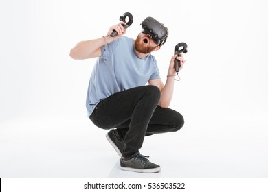 Photo of scared bearded man wearing virtual reality device standing over white background.