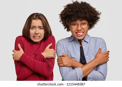 Photo of scared multiethnic females cross hands over chest, feel cold and embarrased, afraid of punishment, clench teeth with fear, stand closely to each other, isolated over white background.