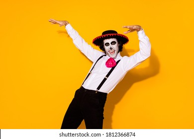 Photo of scary zombie creature guy jump scare raise pretend hands tree branches horror movie casting wear white shirt death costume sugar skull suspenders isolated yellow color background