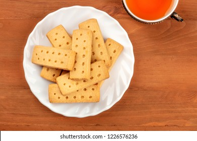 A photo of Scottish shortbreads, butter cookies, shot from the top on a rustic background with a vintage tea cup and copy space