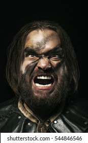 Photo of screaming viking warrior on black background.