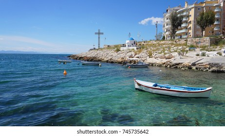 Photo of seascape near Marina Zeas with picturesque small chapel and beautiful spring flowers, Peiraeus, Attica, Greece
