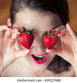 Photo of seductive female holding red strawberry near face eyeys