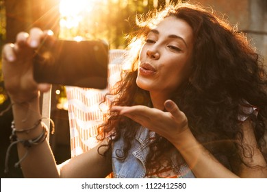 Photo of seductive flirty woman 18-20 smiling and blowing air kiss at cell phone while taking selfie photo during rest in lounge chair in park on sunny day
