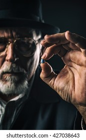 Photo of a senior adult male drug pusher showing off a potent blue pill