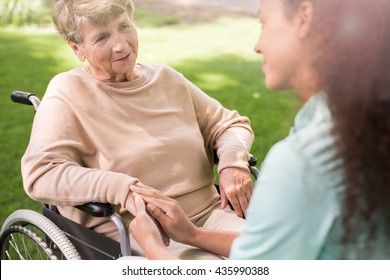 Photo of senior lady on wheelchair with carer outdoor