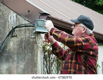 photo senior male glasses working outside doing repairs
