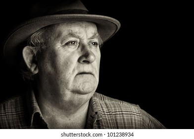 photo senior male retired wearing a hat on black. old man with character in his face. black and white acting mood, sad, lonely, Dementia portrait.