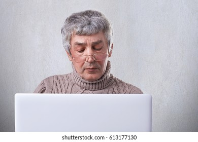 A photo of senior man with gray hair and wrinkles focused on the screen of his laptop. Pensive mature man in eyeglasses working with computer with internet wireless isolated over white background.