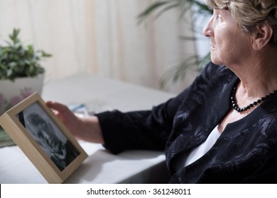 Photo of senior widow reminiscing her dead husband