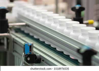 Photo sensor detect medicine bottles on line conveyor in pharmaceutical industry. Industrial Machine for quality of medical product in line conveyor processing. Industrial and technology concept.