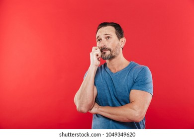 Photo of sensual man 30s in casual t-shirt looking upward and thinking or remembering isolated over red background