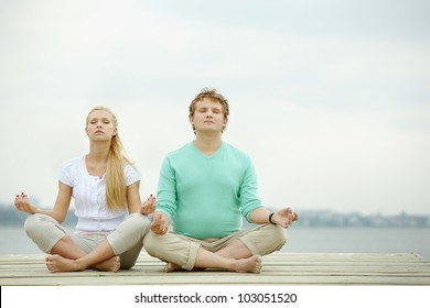Photo of serene couple meditating outdoors
