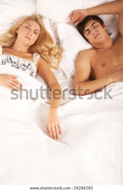 Photo of serene woman and man lying in bed and sleeping