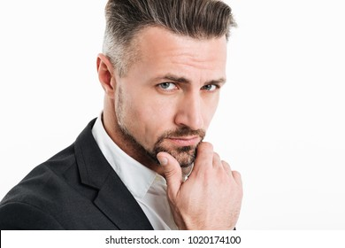 Photo of serious bearded businessman in suit looking on camera with smart look and touching his chin isolated over white background