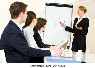Photo of serious business people listening to female manager pointing at whiteboard while presenting new project