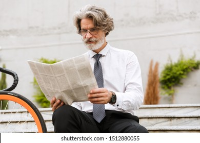 Photo of serious elderly businessman in eyeglasses reading newspaper while sitting with bicycle outdoors