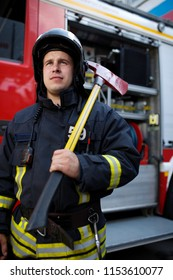 Photo of serious fireman with hammer on background of fire engine at station