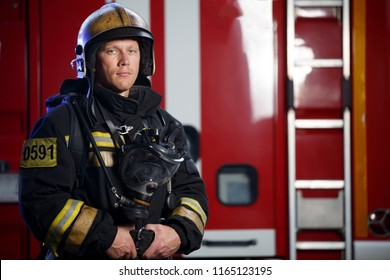 Photo of serious fireman wearing helmet with gas mask on background of fire engine with stair