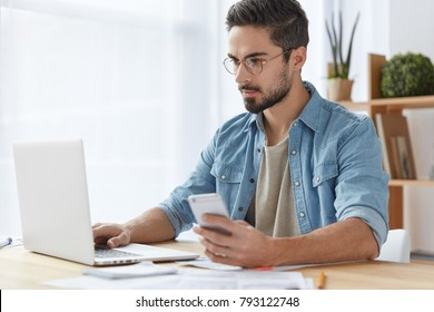 Photo of serious focused man with beard and mustache uses modern digital smart phone device, chats in social networks, keyboards on laptop computer, reads news on websites, makes payment online
