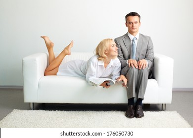 Photo of serious man sitting on sofa with happy woman with magazine lying near by