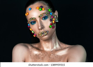 photo session of the girl in the studio on a black background with candymeal face Skittles