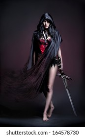 photo session in studio of the young girl in style art with an unusual makeup �  girl in cloak and sword