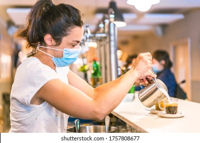 Photo session with a waitress with a face mask in a bar. New normality, security measures after the coronavirus pandemic, social distance, covid-19. Making a milk decaf