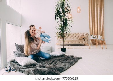 Photo session of a young mother with her daughter in a cozy home environment.