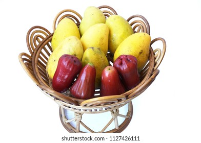 A photo of set of fruits on rattan tray, rose apples fruit or chomphu and ripe mangoes isolated on white background
