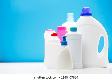 Photo of several bottles of cleaning products on white table isolated on blue background, place for inscription
