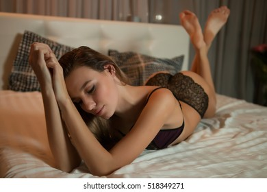 Photo of sexual blond woman lying in bed. Perfect fitness body.