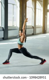 Photo of sexy athletic sporty woman posing in spacy gym with panoramic windows. Having strong, fit body with heatlthy tanned skin and muscles. Doing fitness, yoga exercises.