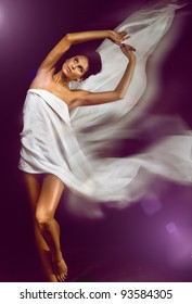 Photo of sexy beautiful woman with white tissue posing on dark background