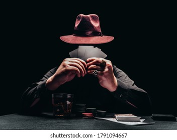 Photo of a shaded gangster in black shirt and hat playing poker and holding black cards with game chips and money.