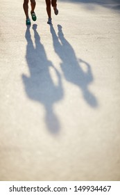 Photo of shadows of dates legs running outdoors
