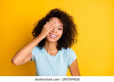 Photo of shiny childish dark skin wavy lady wear blue t-shirt arm cover eye isolated yellow color background
