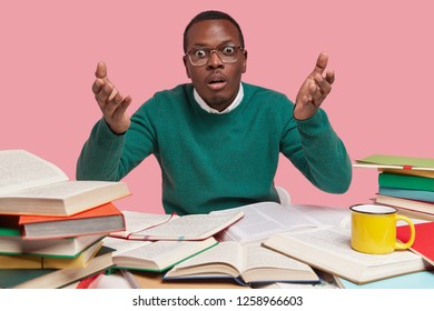 Photo of shocked black man raises hands in bewilderment, has wide opened eyes, dressed in green jumper, translates foreign article, uses many thick dictionaries, drinks hot tea, poses at desktop
