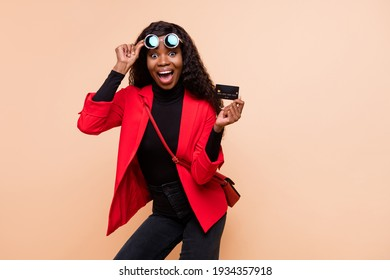 Photo of shocked brown haired afro american woman wear glasses hold debit card isolated on beige color background