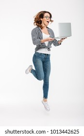 Photo of shocked happy young lady jumping isolated over white wall background using laptop computer. Looking aside.