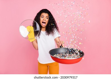 Photo of shocked impressed dark skin woman dressed t-shirt glove scared shooting confetti fryingpan isolated pink color background