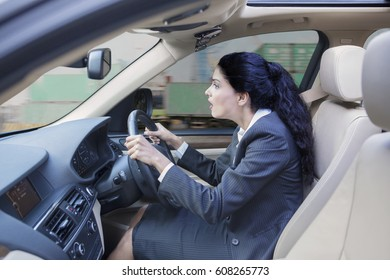Photo of a shocked Indian businesswoman driving a car while looking at the road