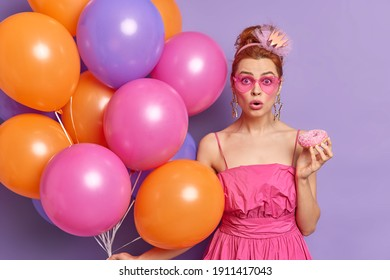 Photo of shocked redhead woman stares through pink shades holds tasty glazed doughnut multicolred balloons finds out shocking news on party isolated over purple background. Festivity concept