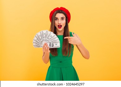 Photo of shocked young woman standing isolated over yellow background holding money. Looking camera pointing.