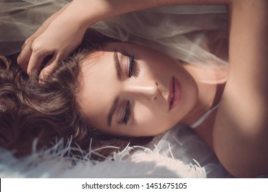 photo shoot in the boudoir style for the beautiful bride in her underwear in the decor of feathers and tulle, tender sensual fashion portraits of the beautiful bride