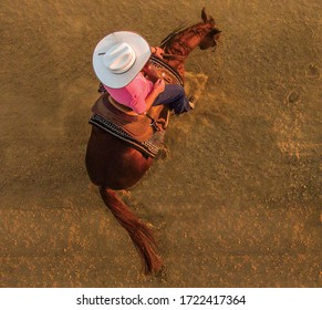 photo shoot seen from above of a cowboy woman riding her horse doing a spin with a hot light in the late afternoon