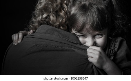 Photo shooting indoors. On a black background. Child hugs his mother.